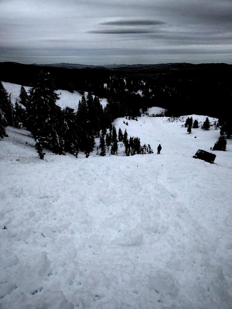 The confluence of debris where the skier was found. The person is standing next to the burial location.