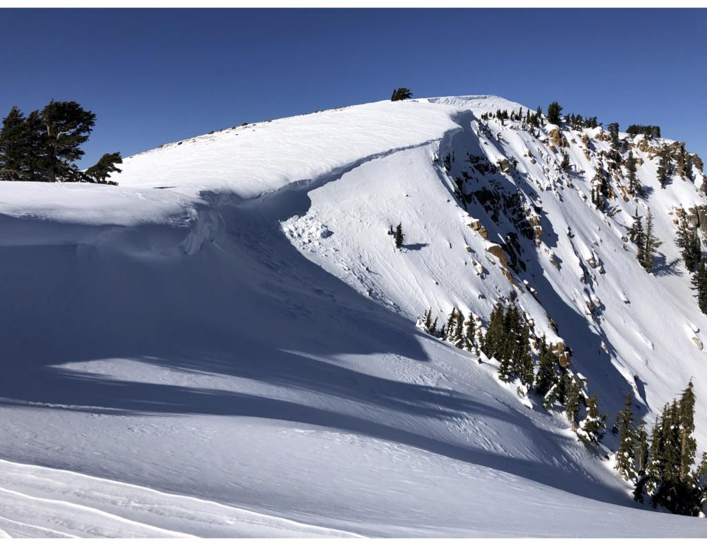 """<a href=""""https://www.sierraavalanchecenter.org/avalanche-terms/cornice"""" title=""""A mass of snow deposited by the wind, often overhanging, and usually near a sharp terrain break such as a ridge. Cornices can break off unexpectedly and should be approached with caution."""" class=""""lexicon-term"""">Cornice</a> <a href=""""https://www.sierraavalanchecenter.org/avalanche-terms/collapse"""" title=""""When the fracture of a lower snow layer causes an upper layer to fall. Also called a whumpf, this is an obvious sign of instability."""" class=""""lexicon-term"""">collapse</a> and wind scour"""
