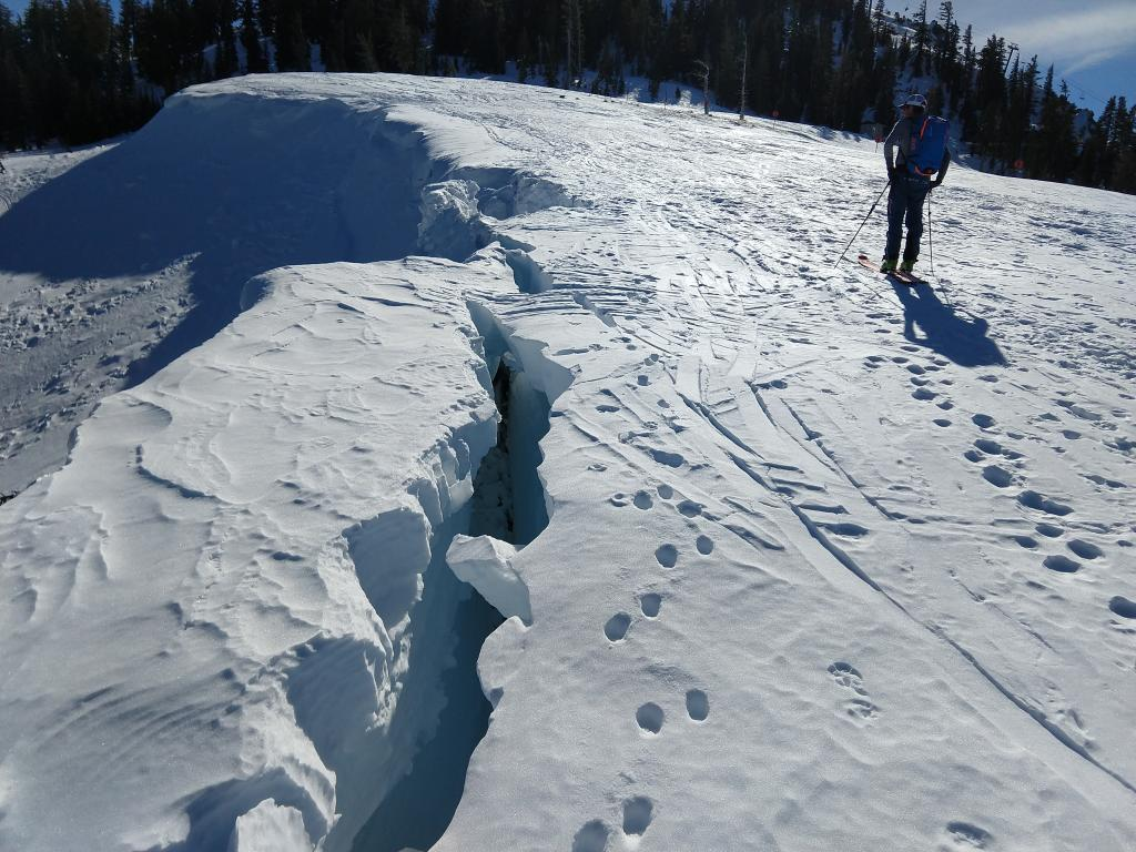 """Large crevasse formed as the <a href=""""https://www.sierraavalanchecenter.org/avalanche-terms/cornice"""" title=""""A mass of snow deposited by the wind, often overhanging, and usually near a sharp terrain break such as a ridge. Cornices can break off unexpectedly and should be approached with caution."""" class=""""lexicon-term"""">cornice</a> pulls away from the ridge during the warm weather."""