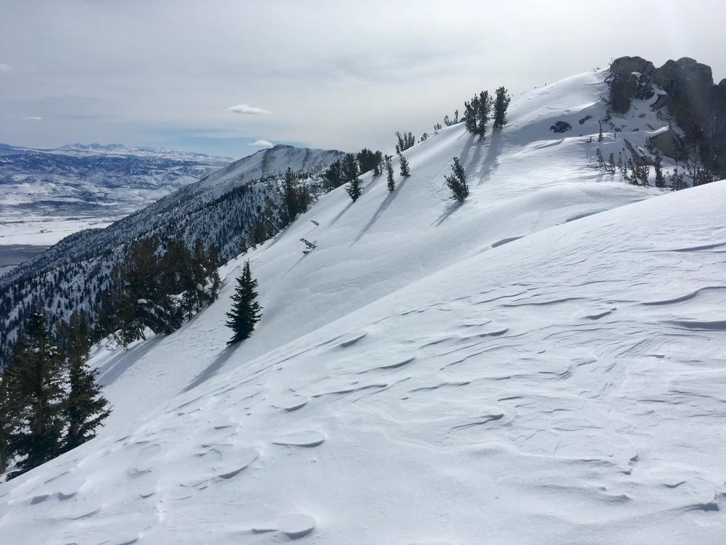 """Wind texture snow in the foreground with small <a href=""""https://www.sierraavalanchecenter.org/avalanche-terms/wind-slab"""" title=""""A cohesive layer of snow formed when wind deposits snow onto leeward terrain. Wind slabs are often smooth and rounded and sometimes sound hollow."""" class=""""lexicon-term"""">wind slabs</a> developing on the opposite slope"""