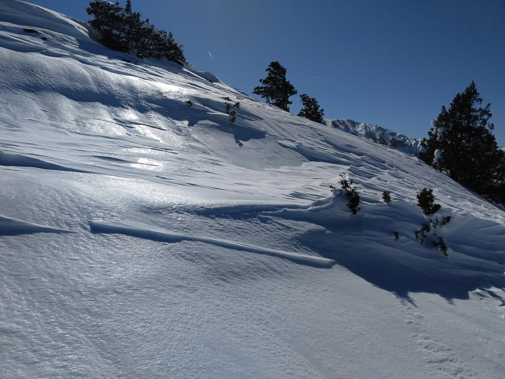 """Variable wind scoured surfaces with exposed <a href=""""https://www.sierraavalanchecenter.org/avalanche-terms/rain-crust"""" title=""""A clear layer of ice formed when rain falls on the snow surface then freezes."""" class=""""lexicon-term"""">rain crust</a> in some areas."""