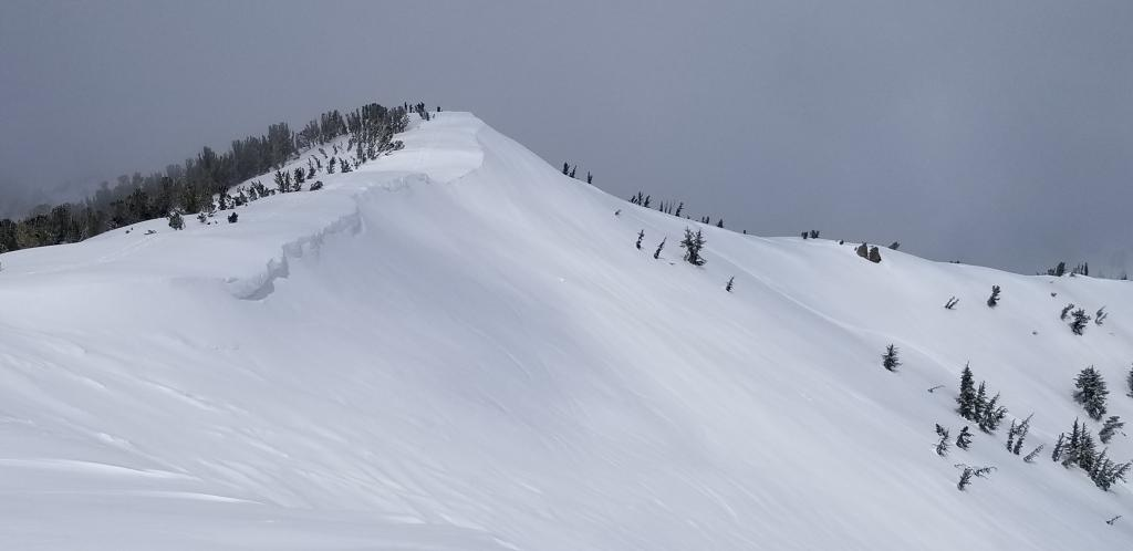 "Small cornices at the top of hourglass bowl, NE <a href=""/avalanche-terms/aspect"" title=""The compass direction a slope faces (i.e. North, South, East, or West.)"" class=""lexicon-term"">aspect</a>"
