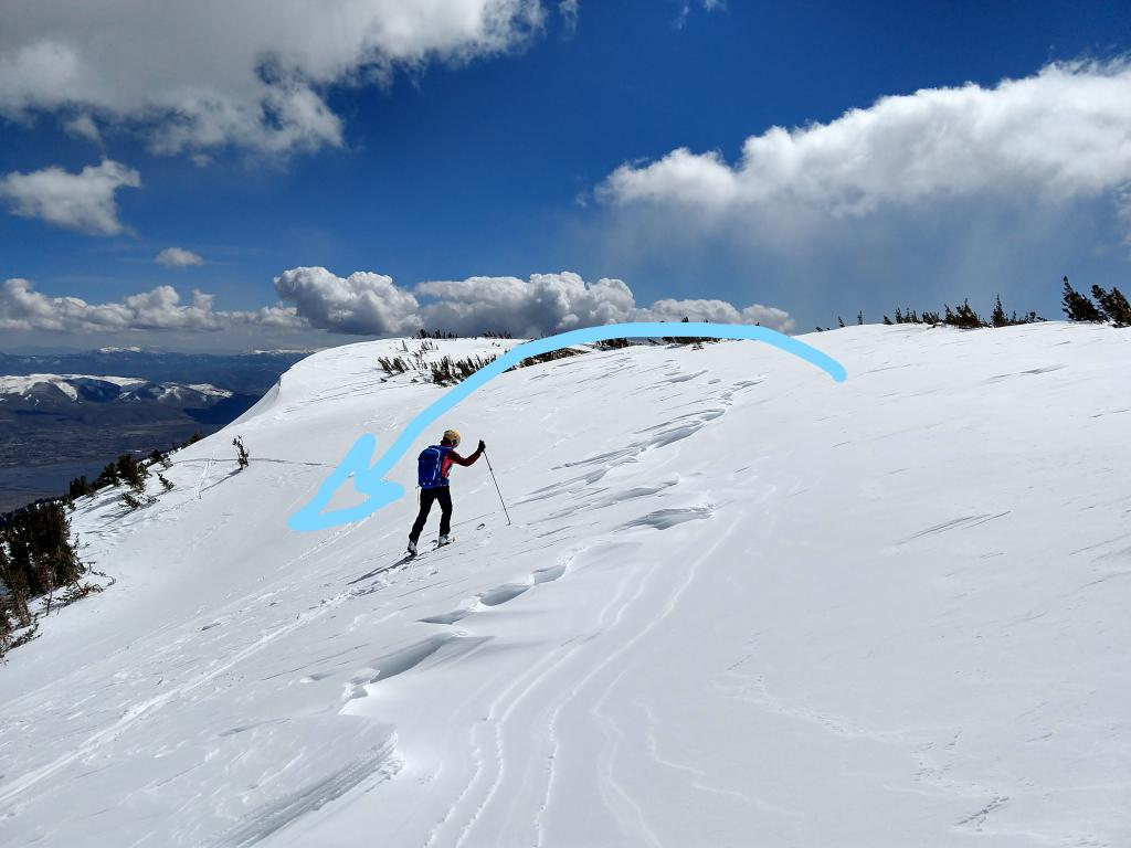 Scoured area along the ridge with a deposition zone for wind transported snow below the skier. The arrow shows the direction that the wind transported the snow during the recent storm.