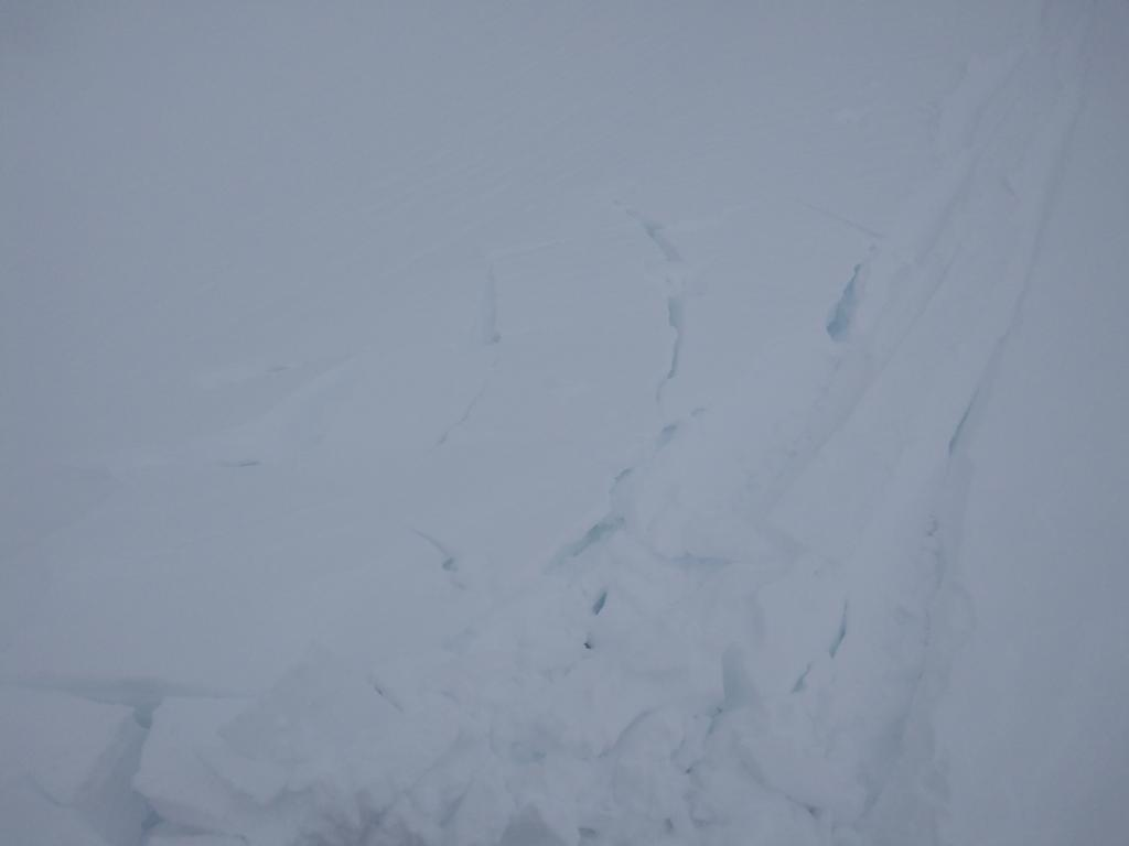 """Minor cracking of <a href=""""https://www.sierraavalanchecenter.org/avalanche-terms/wind-slab"""" title=""""A cohesive layer of snow formed when wind deposits snow onto leeward terrain. Wind slabs are often smooth and rounded and sometimes sound hollow."""" class=""""lexicon-term"""">wind slab</a>."""