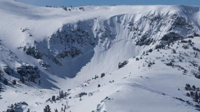 """Upon closer inspection, a large <a href=""""/avalanche-terms/crown-face"""" title=""""The top fracture surface of a slab avalanche. Usually smooth, clean cut, and angled 90 degrees to the bed surface."""" class=""""lexicon-term"""">crown</a> is visible crossing the entire bowl."""